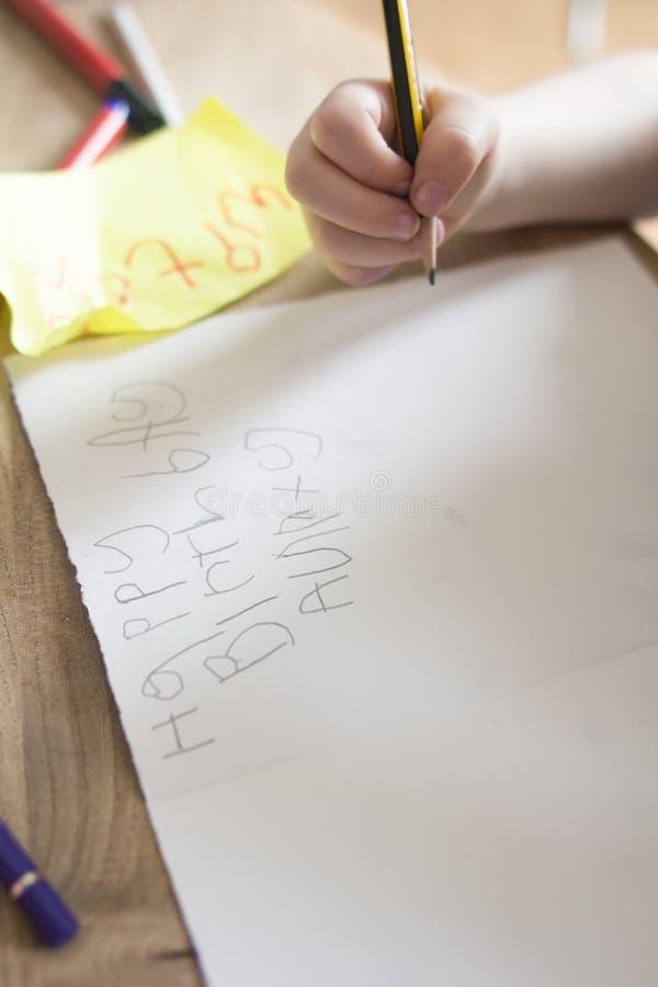 Ett småbarn skriver ut ett födelsedagkort till hennes liten tant arkivbild