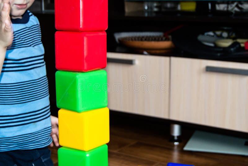 Ett småbarn som spelar med färgrika kuber, bygger ett torn, begreppet av den tidiga utbildningsförberedelsen för utvecklingen av arkivbilder