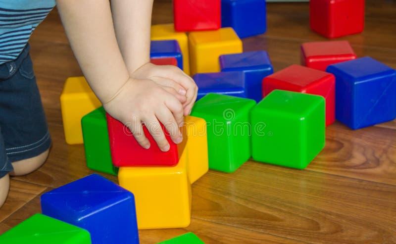 Ett småbarn som spelar med färgrika kuber, bygger ett torn, begreppet av den tidiga utbildningsförberedelsen för utvecklingen av royaltyfria foton