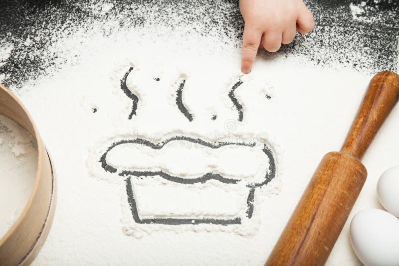 Ett småbarns hand drar en paj eller en kaka med vitt mjöl i köket arkivbilder