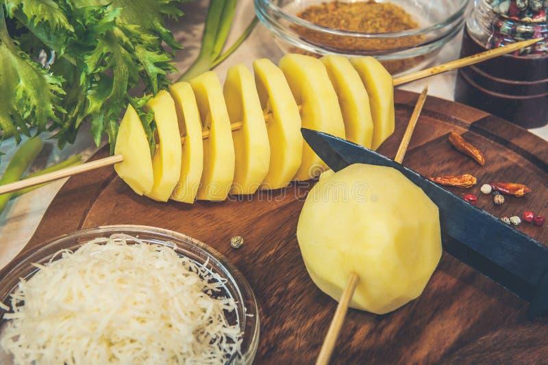 Ett snitt för rå potatis in i en spiral på en steknål med ost, vitlök, örtkryddor och grön sallad Ovanlig maträtt Matlagning för  royaltyfria foton