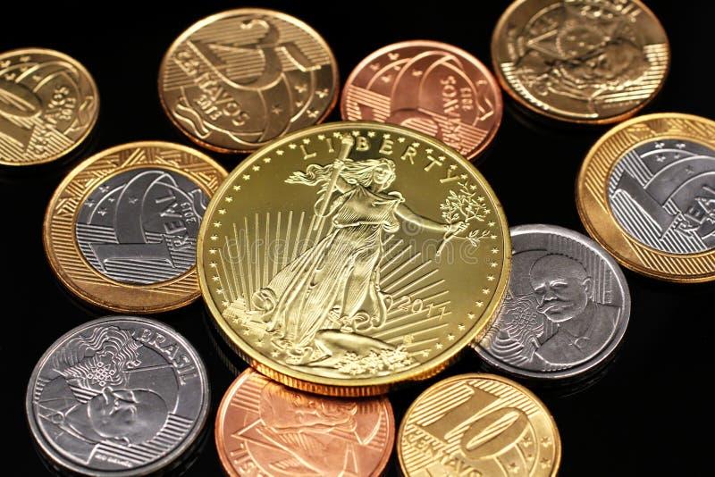 Ett sortiment av brasilianska mynt på en svart reflekterande bakgrund med ett amerikanskt ett guld- mynt för uns fotografering för bildbyråer