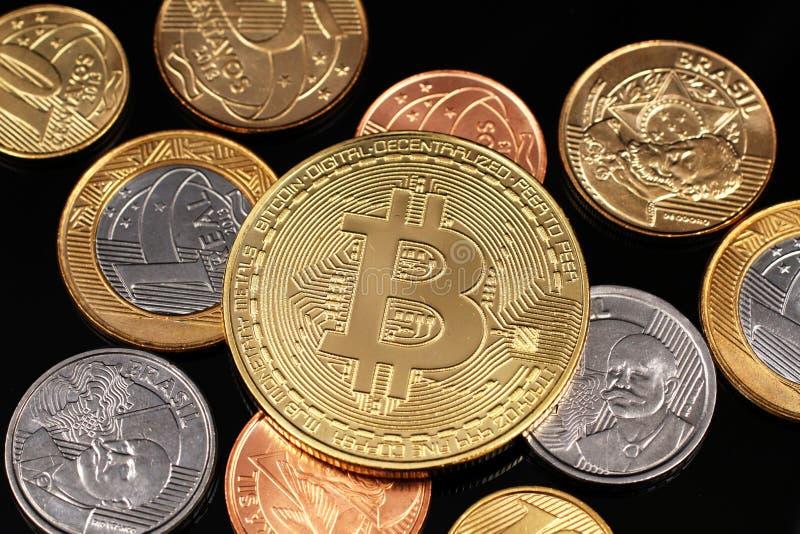 Ett sortiment av brasilianska mynt på en svart reflekterande bakgrund med en guld- fysiska Bitcoin royaltyfria foton