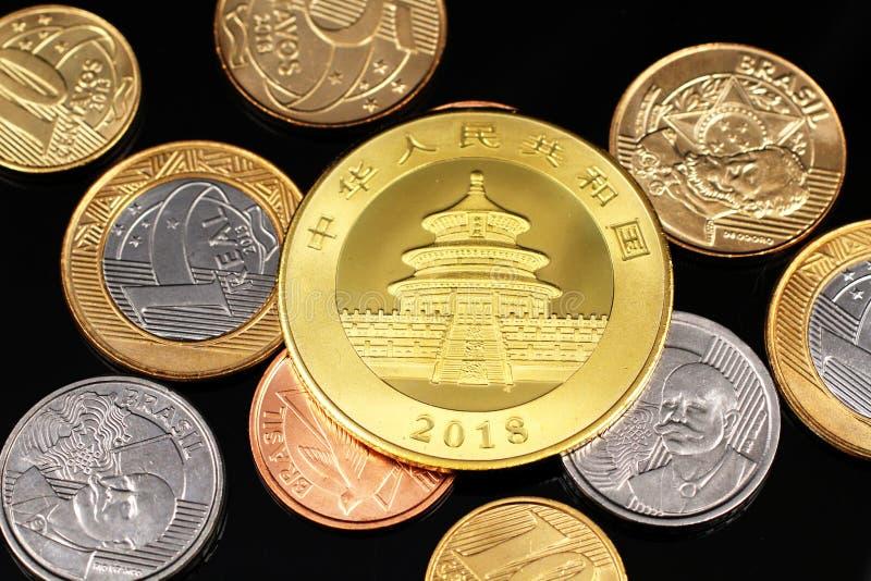 Ett sortiment av brasilianska mynt på en svart reflekterande bakgrund med ett kinesiskt ett guld- mynt för uns fotografering för bildbyråer