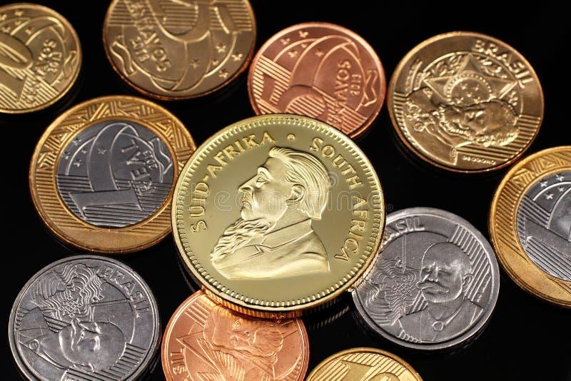 Ett sortiment av brasilianska mynt på en svart reflekterande bakgrund med ett södra - afrikan ett guld- krugerrandmynt för uns royaltyfria foton