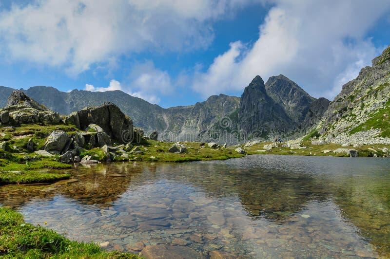 Ett spektakulärt landskap av en sjö i Retezat berg, Rumänien arkivfoto