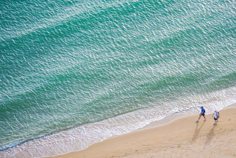 Ett sportpar promenerar stranden fotografering för bildbyråer