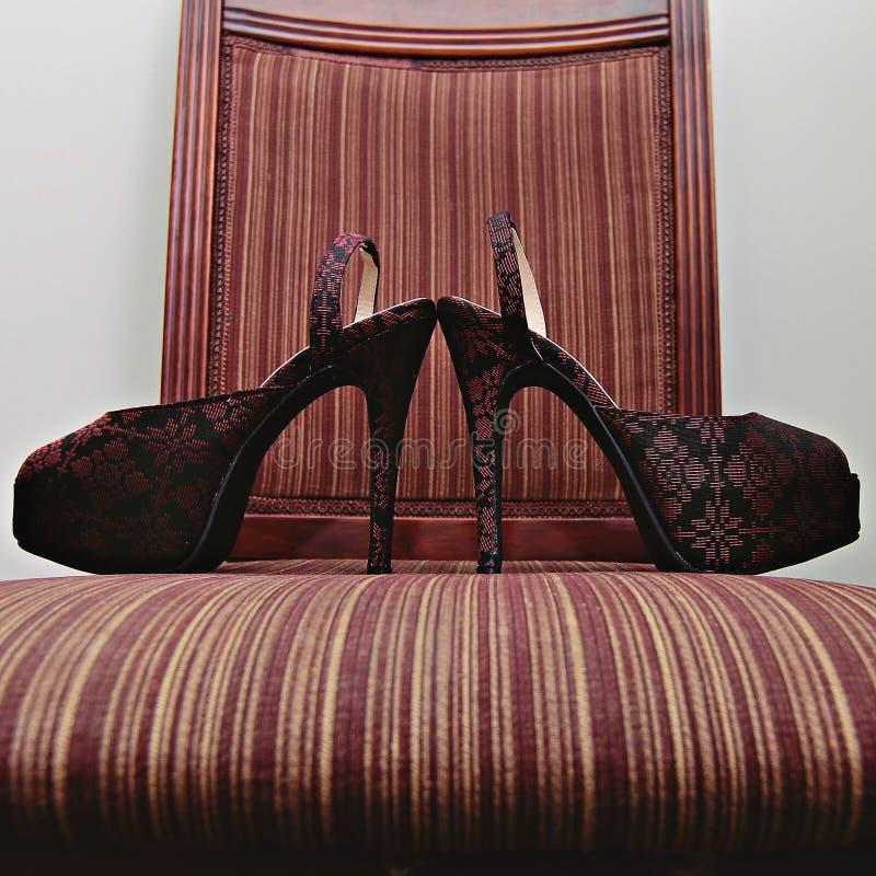 Ett ställe för hög häl för brud på en stol royaltyfri foto