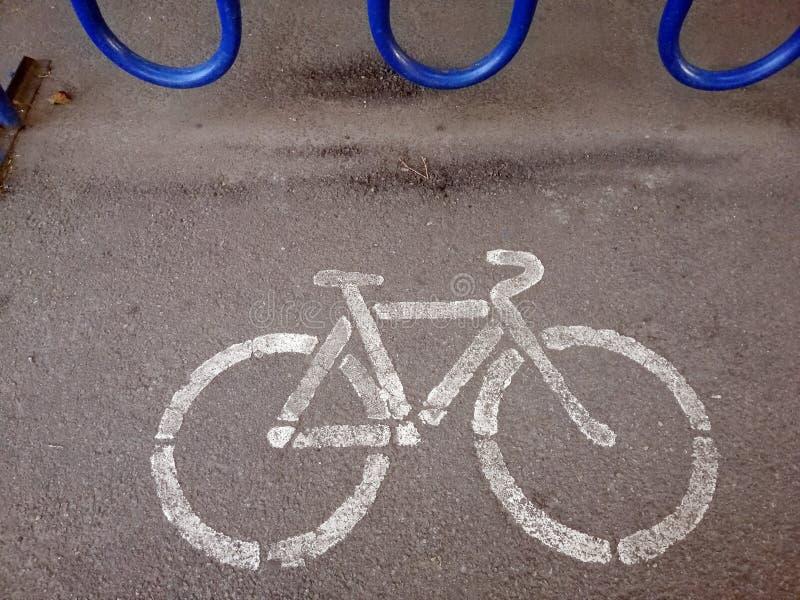 Ett ställe som parkerar cyklar, är ett tecken på asfalten fotografering för bildbyråer