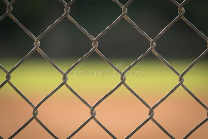 Ett staket för chain sammanlänkning med en suddig bakgrund av ett baseballfält arkivfoton