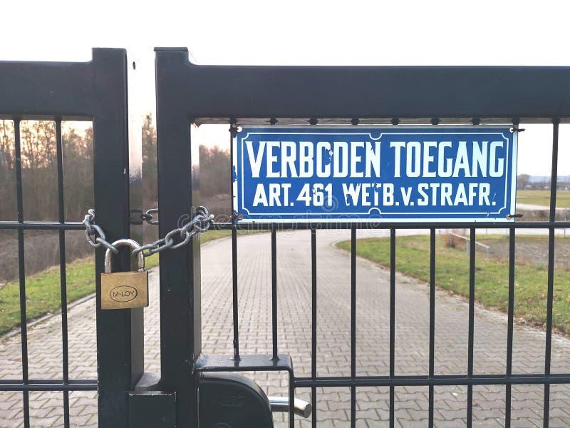 Ett staket med ett lås och ett tecken som säger inget låtet tillträde arkivbild