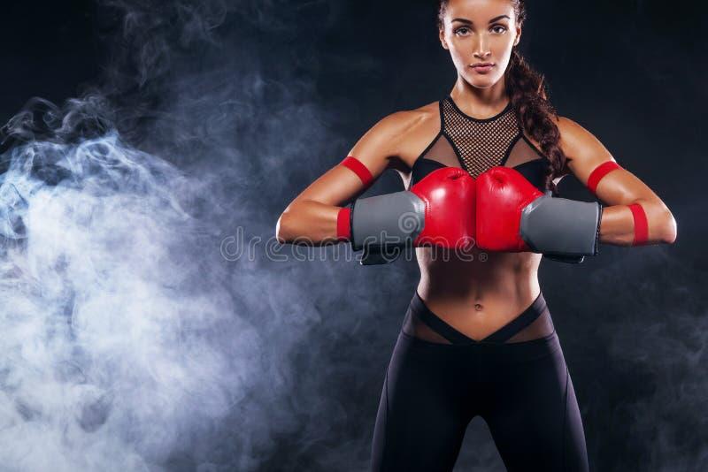 Ett starkt idrotts-, kvinnaboxare som boxas på utbildning på den svarta bakgrunden Sportboxningbegrepp med kopieringsutrymme royaltyfri fotografi