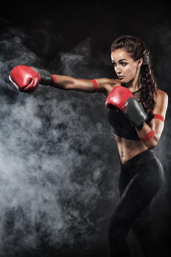 Ett starkt idrotts-, kvinnaboxare som boxas på utbildning på den svarta bakgrunden Sportboxningbegrepp med kopieringsutrymme arkivfoton