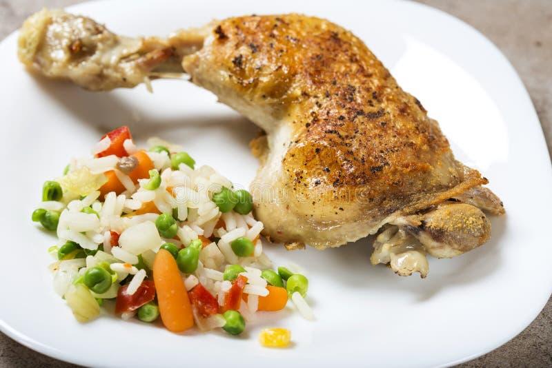 Ett stekt kycklingben med kokta grönsaker gillar ris, grön pe arkivfoto