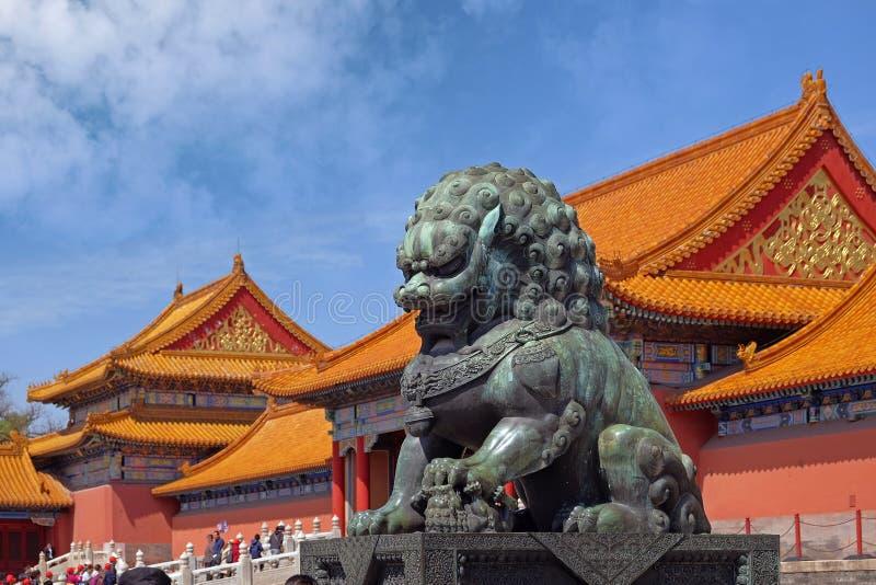 Ett stenlejon som framme förläggas av de inre portarna av slottmuseet Forbidden City i Peking, Kina fotografering för bildbyråer