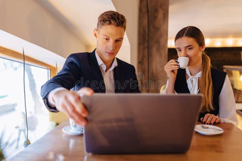 Ett stilfullt par dricker morgonkaffe på kafét och arbetar med en bärbar dator, unga affärsmän och freelancers arkivfoto