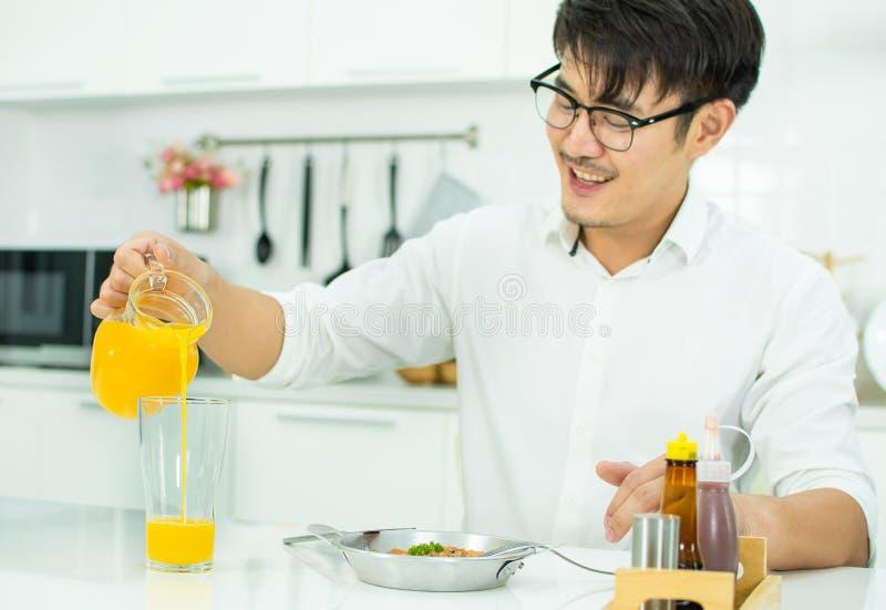 Ett stiligt h?ller den orange fruktsaften till exponeringsglaset royaltyfri fotografi