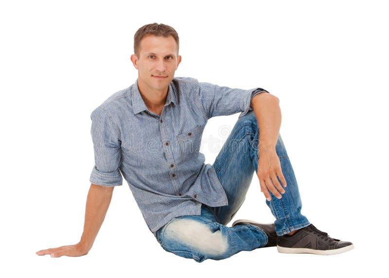Ett stiligt sammanträde för ung man på golvet royaltyfria bilder