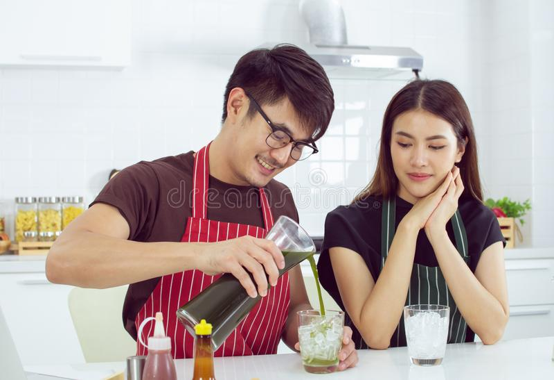 Ett stiligt tar att bry sig hans gulliga flickvän, genom att hälla grönt te för henne arkivbild