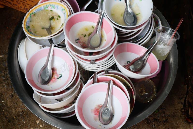 Ett stort antal använda matkoppar staplas tillsammans i en behållare som väntar för att tvätta sig arkivbild