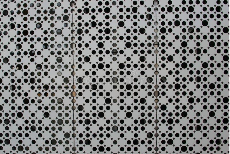 Ett stort antal hål på ett ark av metall royaltyfri foto