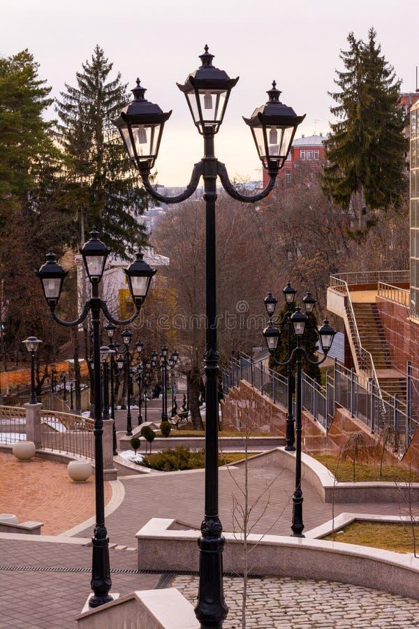 Ett stort antal nattlyktor på sidorna av en belagd med tegel trappuppgång som leder ner - en semesterortstad, cityscape royaltyfria foton