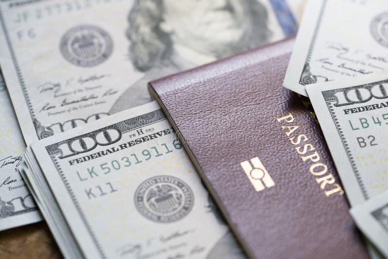Ett stort belopp av 100 US dollarpengaranm?rkningar ?verst av en bunt av pass royaltyfri bild