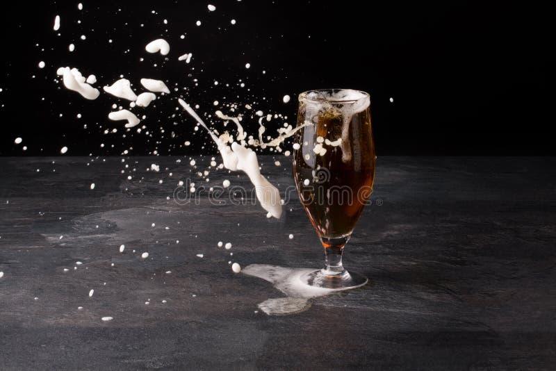 Ett stort exponeringsglas av öl mycket med brunt öl och med vitt skum blowed bort på en mörk stenbakgrund Alkoholdryck arkivfoton