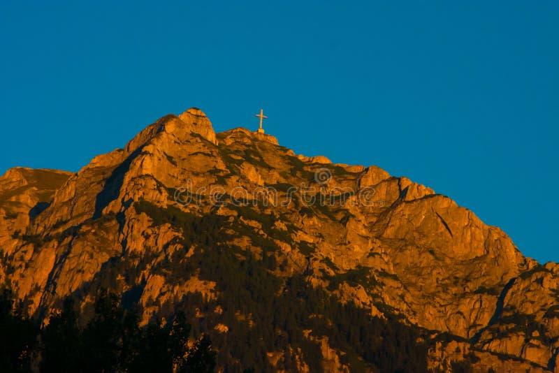 Ett stort kors står på kullen på solnedgången royaltyfria foton