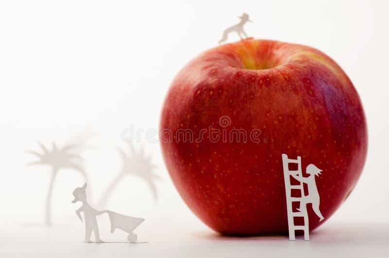 Ett stort rött äpple med små pappers- människor arkivbilder