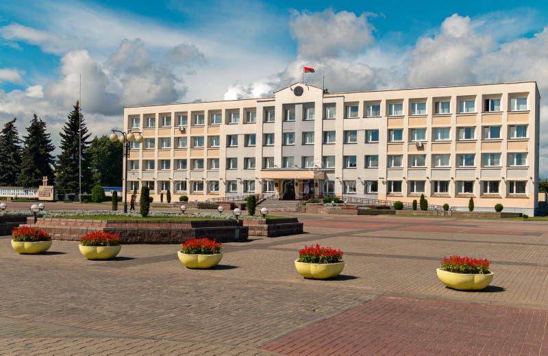 Ett stort rent område som är främst av en kontorsbyggnad med blommakrukor Vinkande nationsflagga på taket mot a royaltyfri fotografi