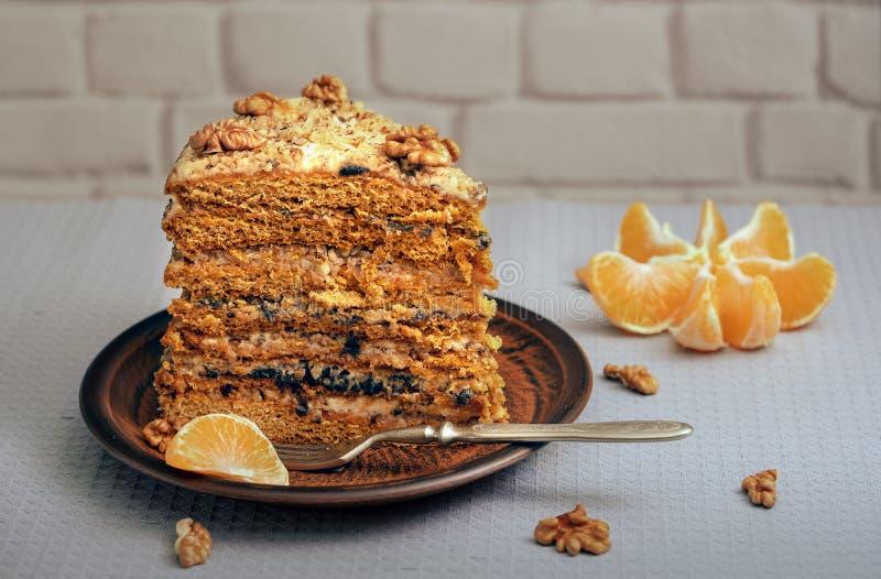 Ett stort stycke av den hemlagade kakan på en keramisk platta med muttrar och mandarinen royaltyfri foto