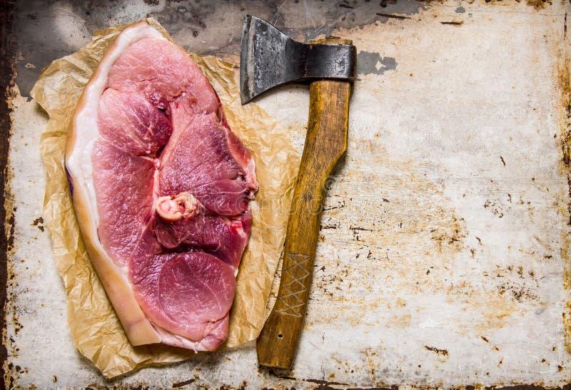 Ett stort stycke av rått griskött med en köttyxa arkivfoton