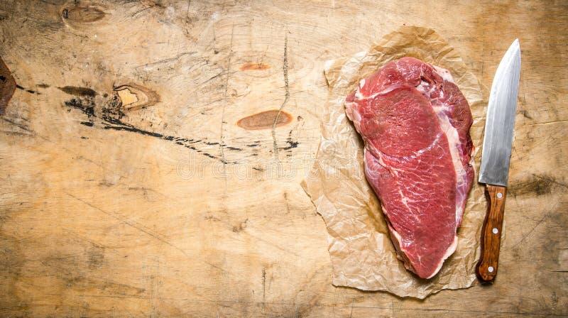 Ett stort stycke av rått kött med en slaktarekniv på papperet royaltyfri foto