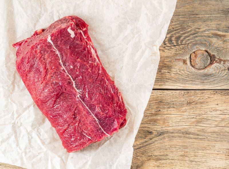 Ett stort stycke av rått kött Nötköttfläskkarré på vitt pergamentPA arkivfoton