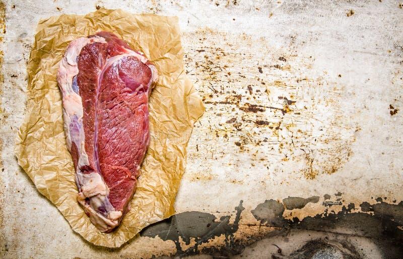 Ett stort stycke av rått nytt kött på papper royaltyfri bild