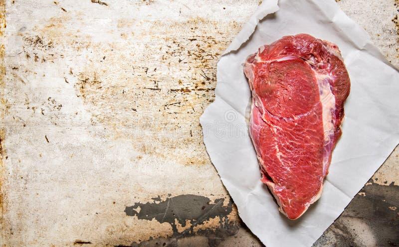 Ett stort stycke av rått nytt kött på papper royaltyfria foton