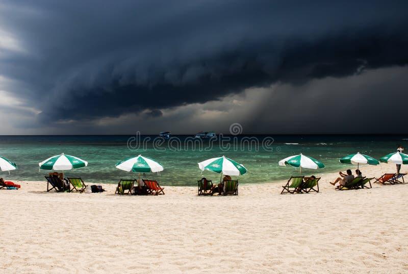 Ett stort svart moln bildar och den vita stranden på Koh Tao, Thailand fotografering för bildbyråer