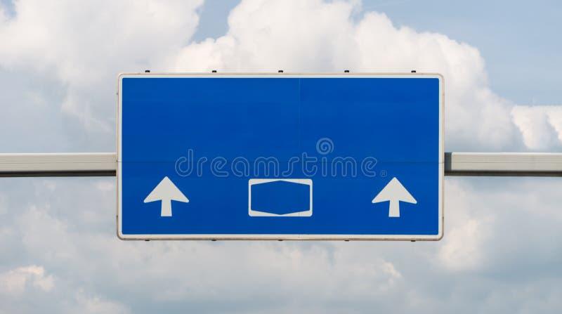 Ett stort vägmärke ovanför en tysk huvudväg i blått, med inga tecken och undertexter, med en snabb bana royaltyfri bild