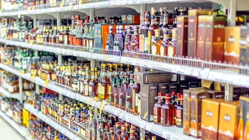 Ett stort val av alkoholdrycker på hyllorna av supermarket Text på ryss: handling rom, tequila, arkivfoto