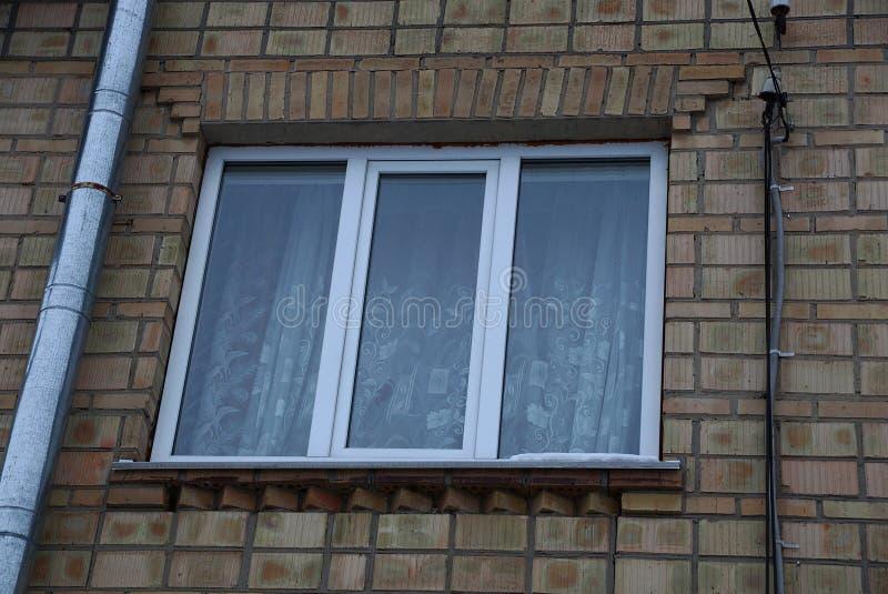Ett stort vitt fyrkantigt fönster på en brun tegelstenvägg med ett metallrör arkivbilder