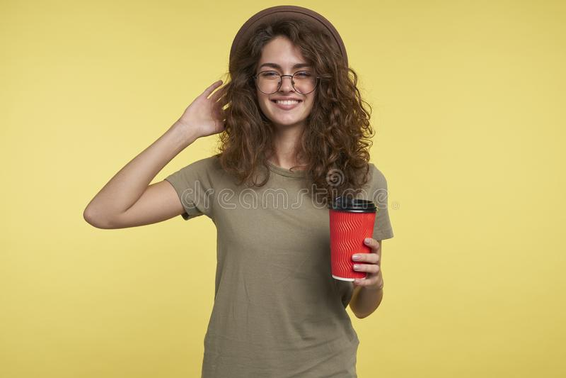 Ett studioskott av den unga studentkvinnan, ler hon och rymma en kaffekopp, en bärande hatt och ett glasögon som över isoleras royaltyfri fotografi