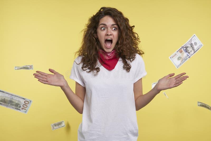 Ett studioskott av kvinnan, som segrar mycket pengar, kassa som faller på hennes huvud som isoleras över gul bakgrund arkivfoto
