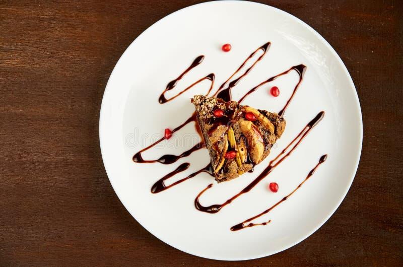 Ett stycke av äpplekakan med vallmo på den vita plattan som dekoreras med nytt granatäpplefrö, choklad Äppelpaj på trätabellen royaltyfria foton