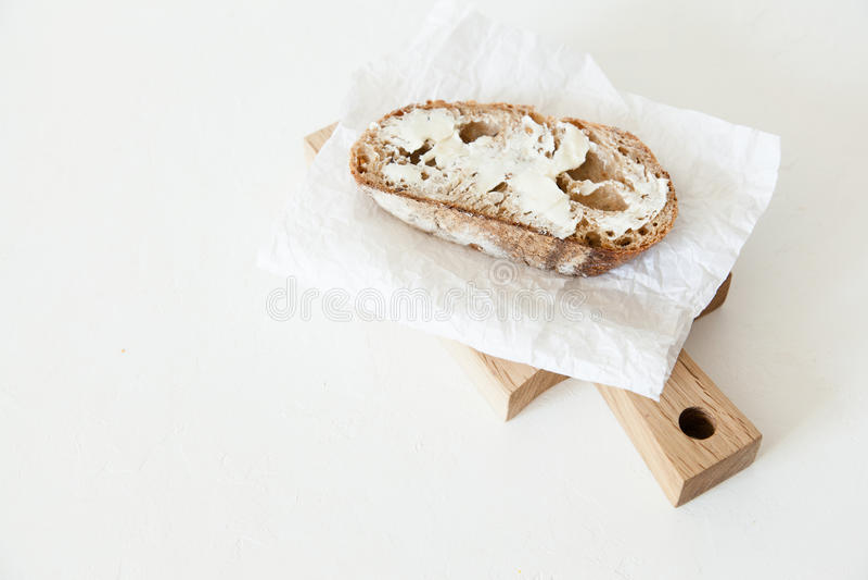Ett stycke av bröd med smör och saltar lögner på ett träbräde på en vit bakgrund royaltyfri bild