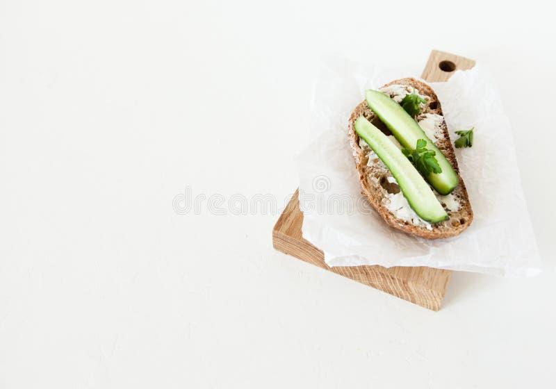 Ett stycke av bröd med smör, saltar med gurkan, och gräsplaner ligger på ett träbräde på en vit bakgrund arkivfoto