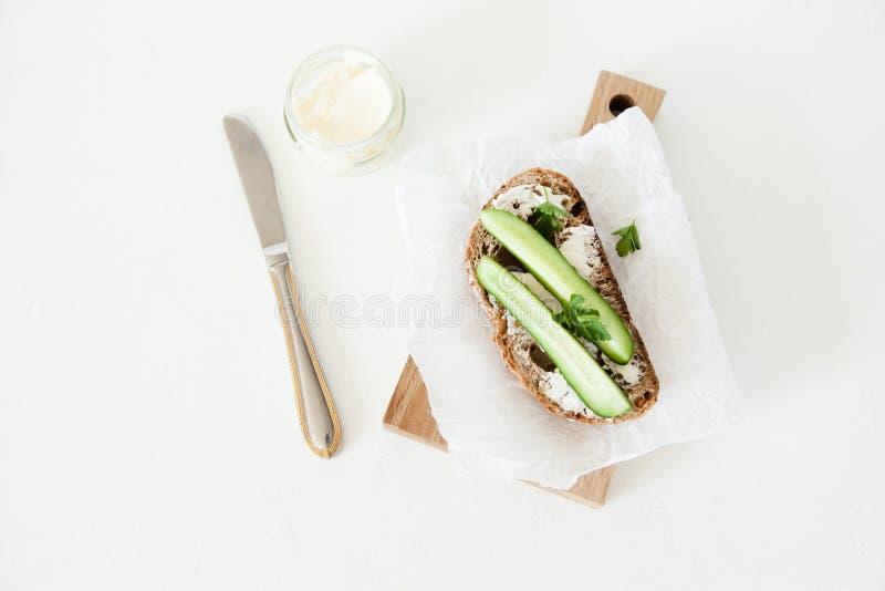 Ett stycke av bröd med smör, saltar med gurkan, och gräsplaner ligger på ett träbräde på en vit bakgrund royaltyfri bild