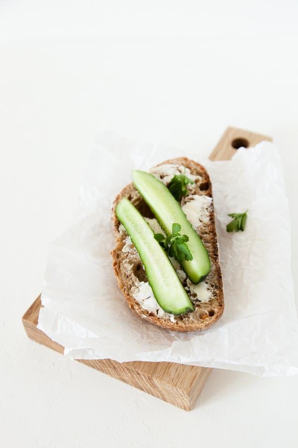 Ett stycke av bröd med smör, saltar med gurkan, och gräsplaner ligger på ett träbräde på en vit bakgrund arkivbild