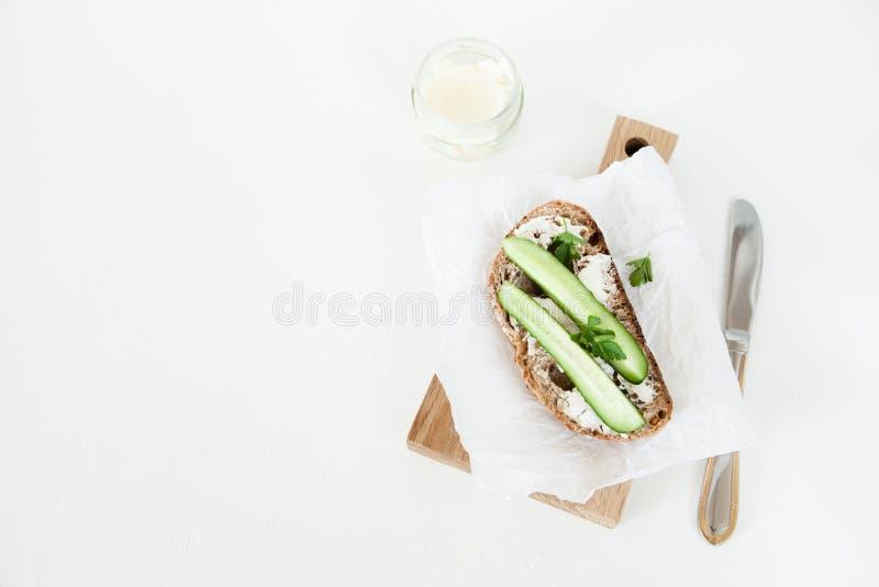 Ett stycke av bröd med smör, saltar med gurkan, och gräsplaner ligger på ett träbräde på en vit bakgrund royaltyfria bilder