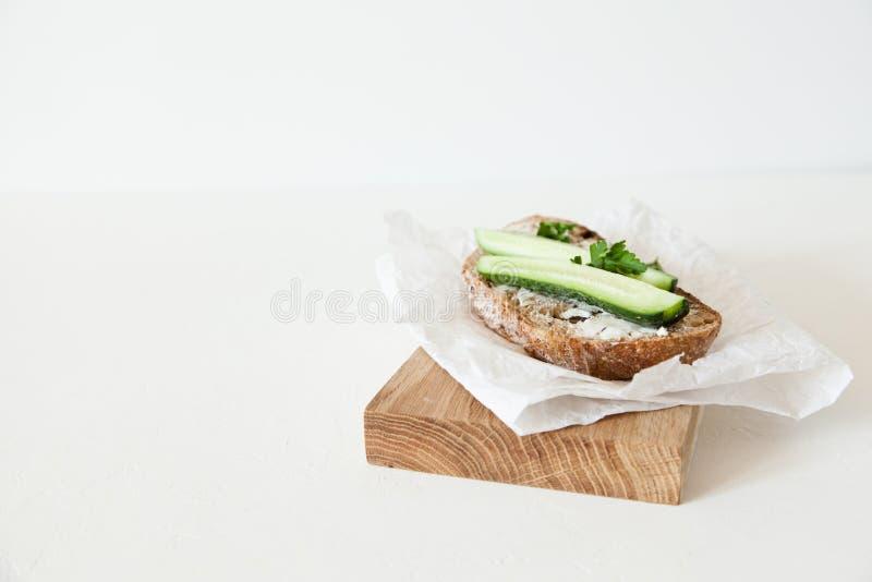 Ett stycke av bröd med smör, saltar med gurkan, och gräsplaner ligger på ett träbräde på en vit bakgrund fotografering för bildbyråer